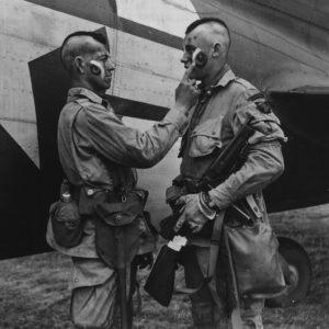 Paratrooper wearing mohawk hairstyle applies war paint