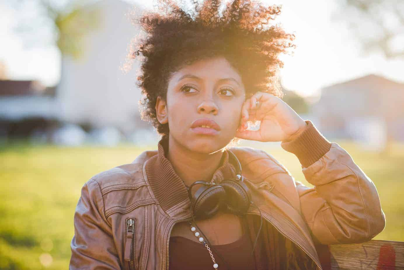 Black girl wearing brown leather jacket with curly hair, standing outside in the sunlight leaning on a fence post.