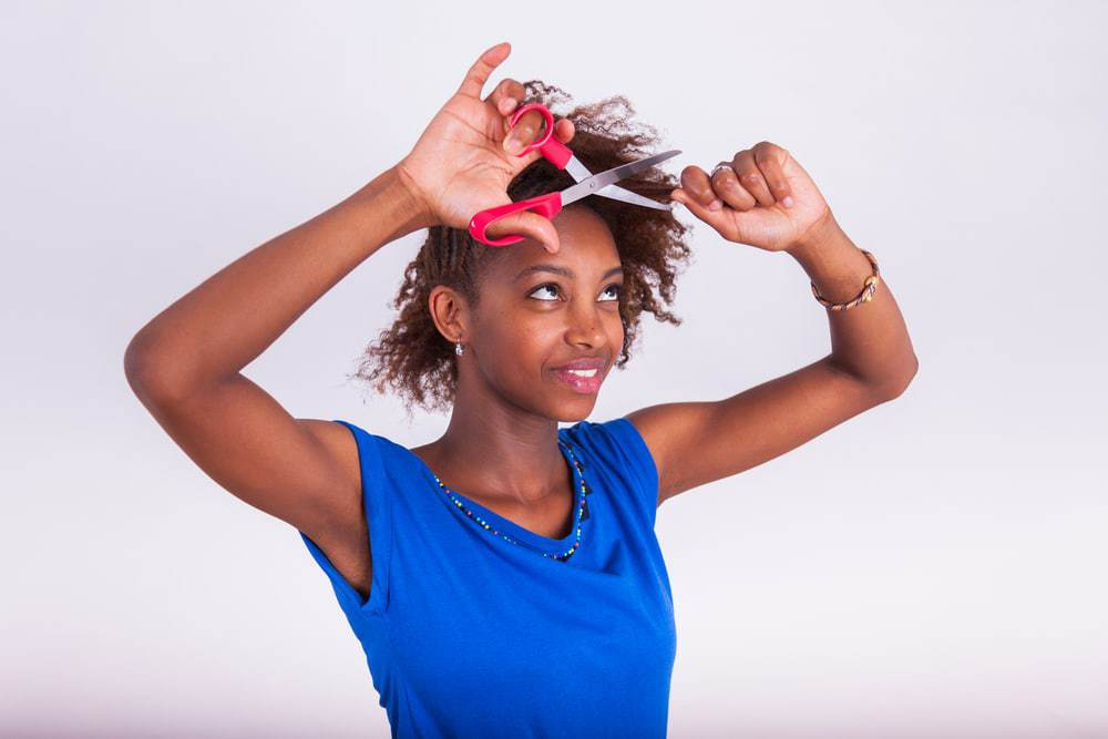 Young African American women cutting her hair