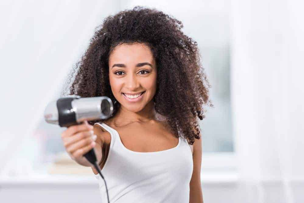 African American women avoiding a hairdryer because she is starting the Curly Girl Method