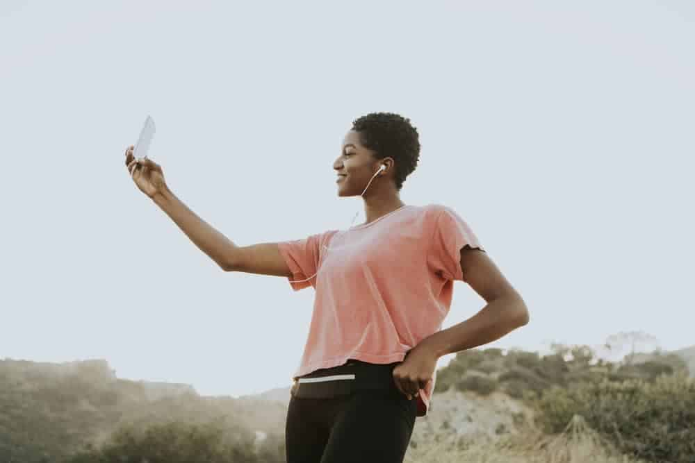 Pretty African American female standing outside taking a selfie with her mobile phone.