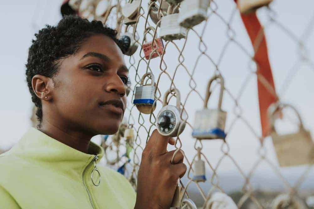 Cute black girl standing outside in front of a fence with padlocks.