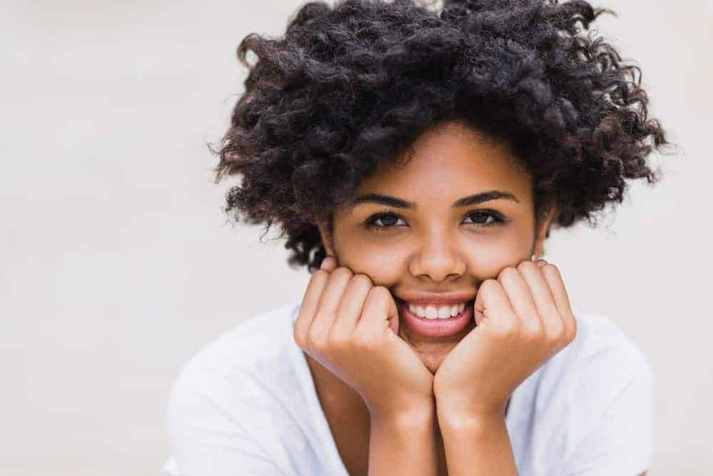 Cute black women showing off her naturally curly hair with a big smile