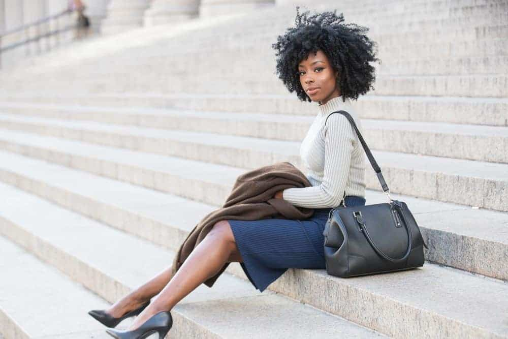 African American female wearing a ribbed sweater, blue skirt, black heals and with beautiful curly hair.
