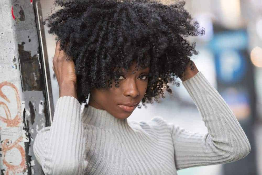 Black woman looking directly into the camera with naturally curly hair wearing a badge ribbed sweater