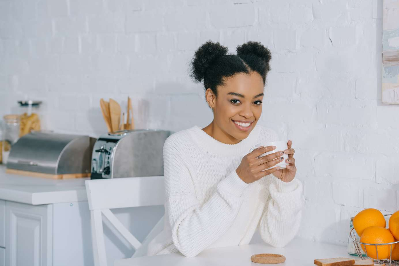 African American lady drinking coffee wearing a white sweater and afro puffs