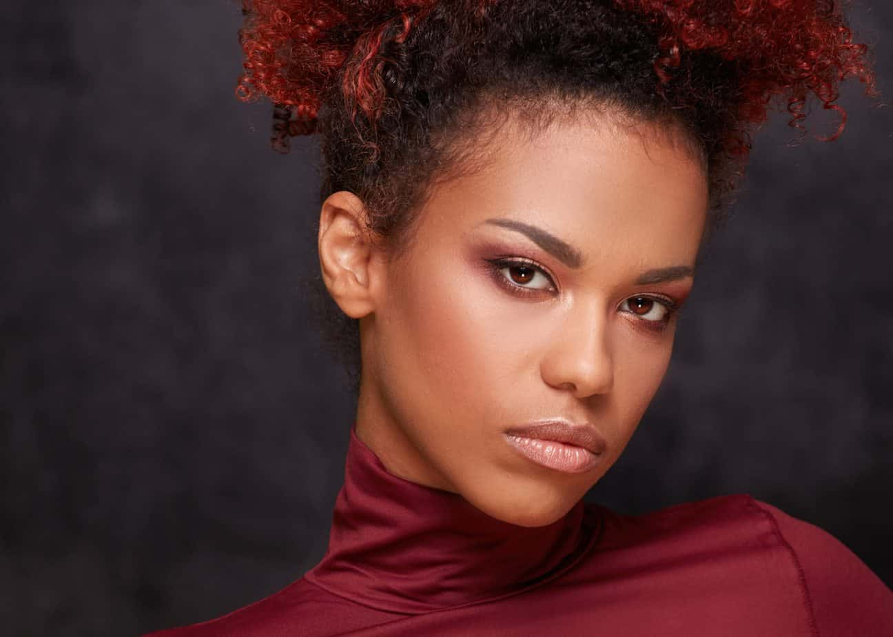 Close-up photo of your African American women wearing a red turtle neck.