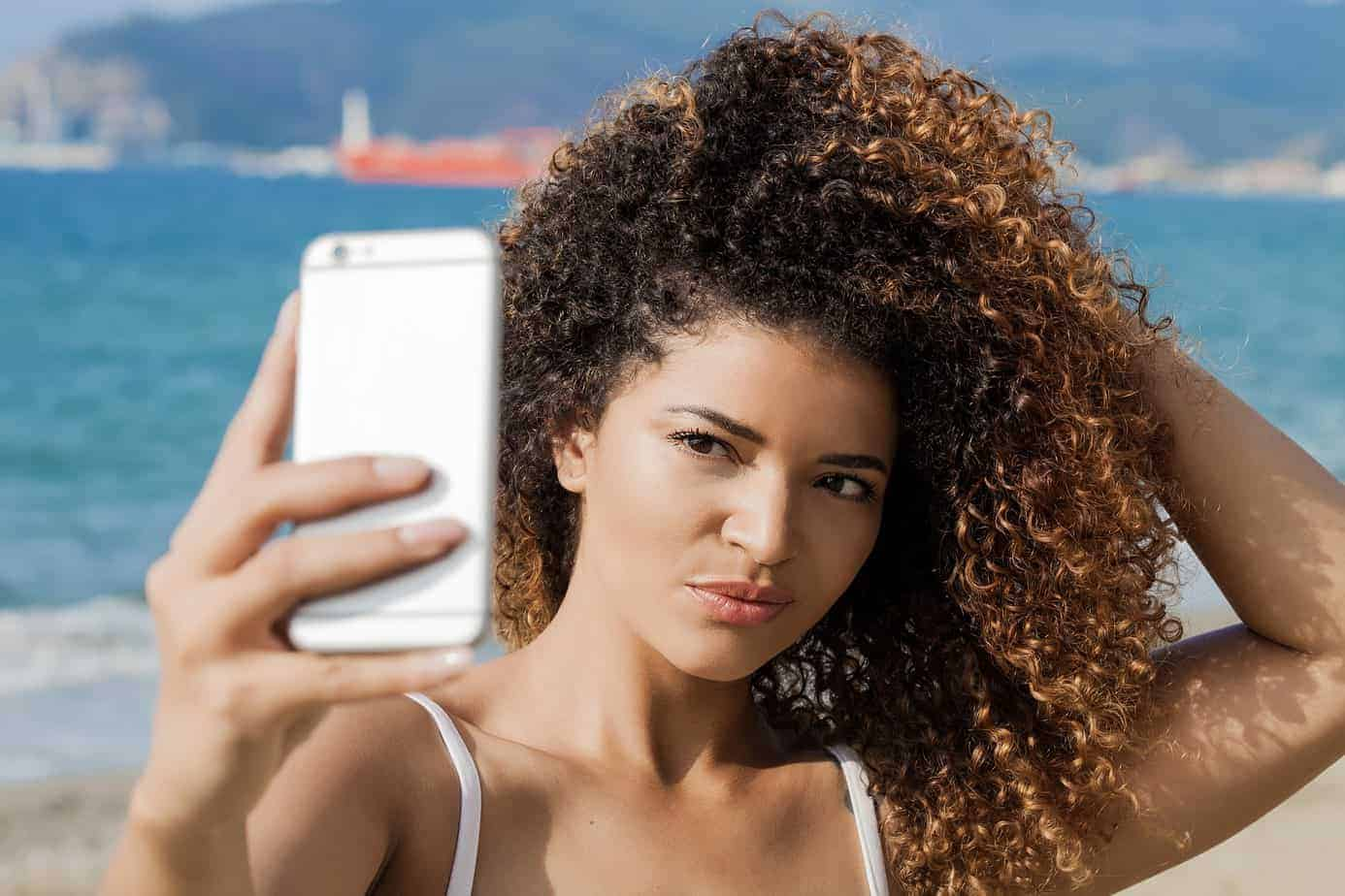 Young, cute woman taking a selfie on the beach with her iPhone after moisturizing her hair with lavender essential oil.