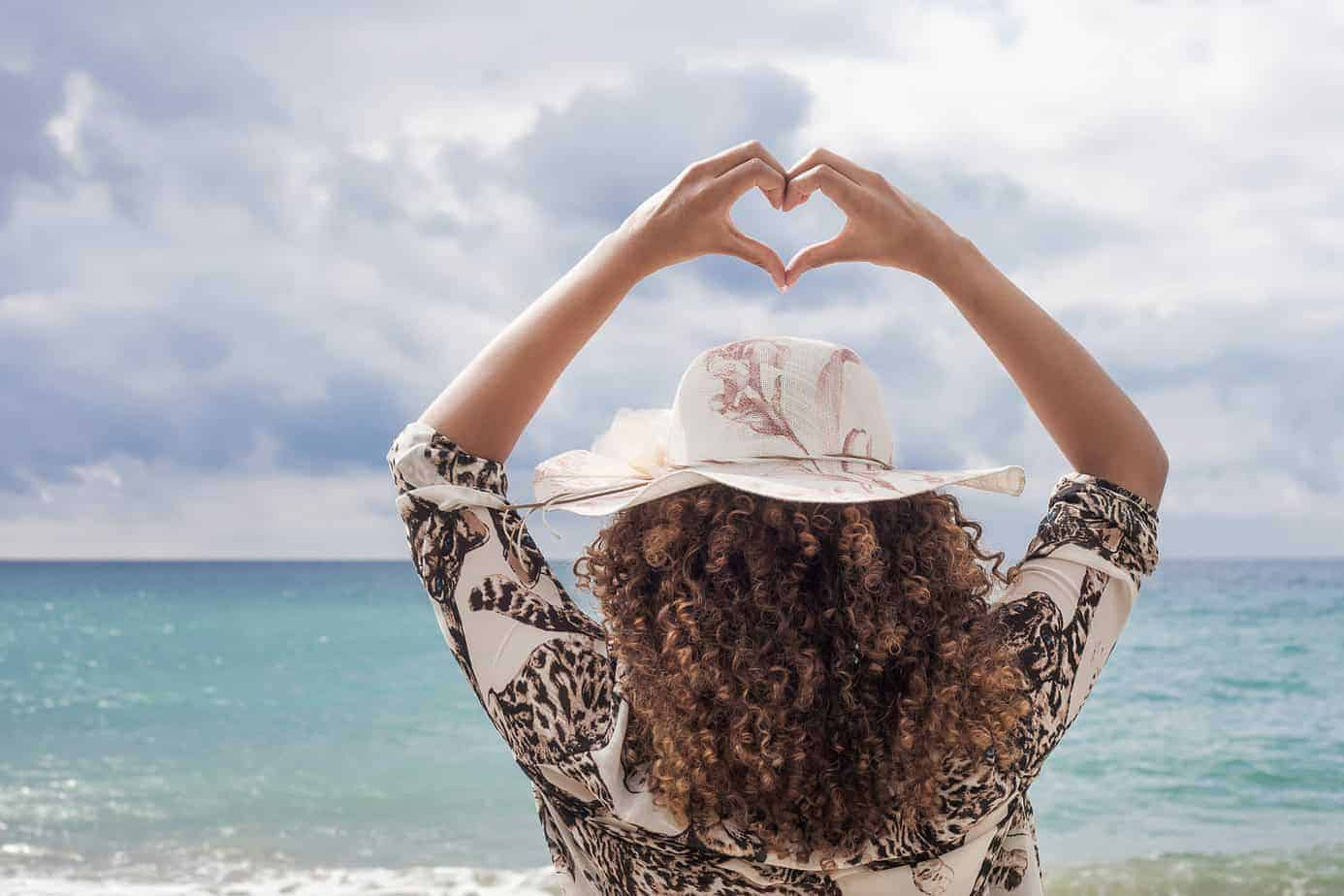 Woman with curly hair that's been conditioned with lavender oil standing on the beach showing a heart symbol.