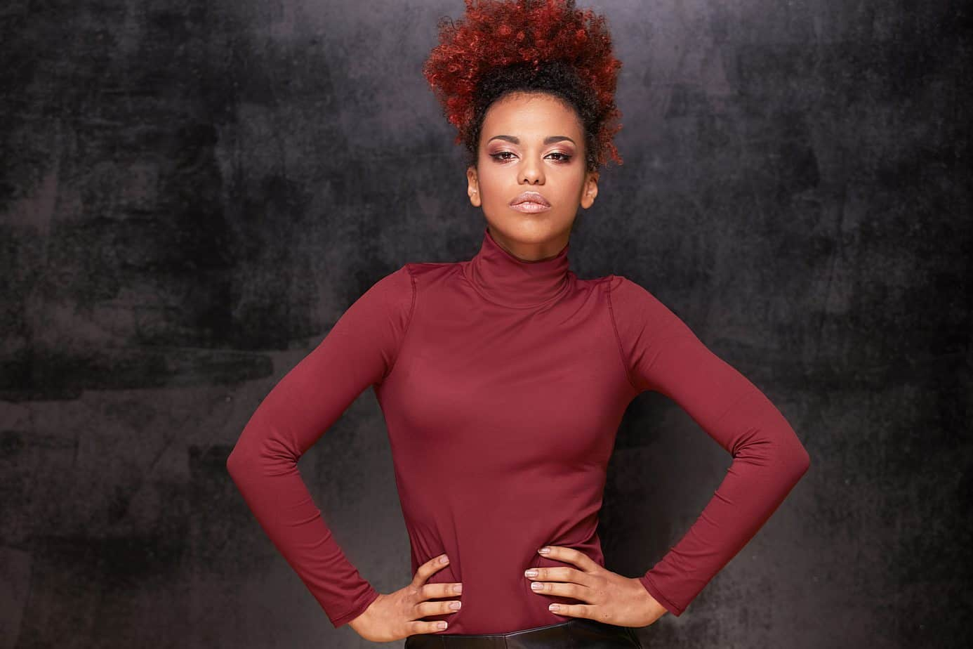 Black women with curly red hair with hands on her hips wearing a red mock turtle neck.