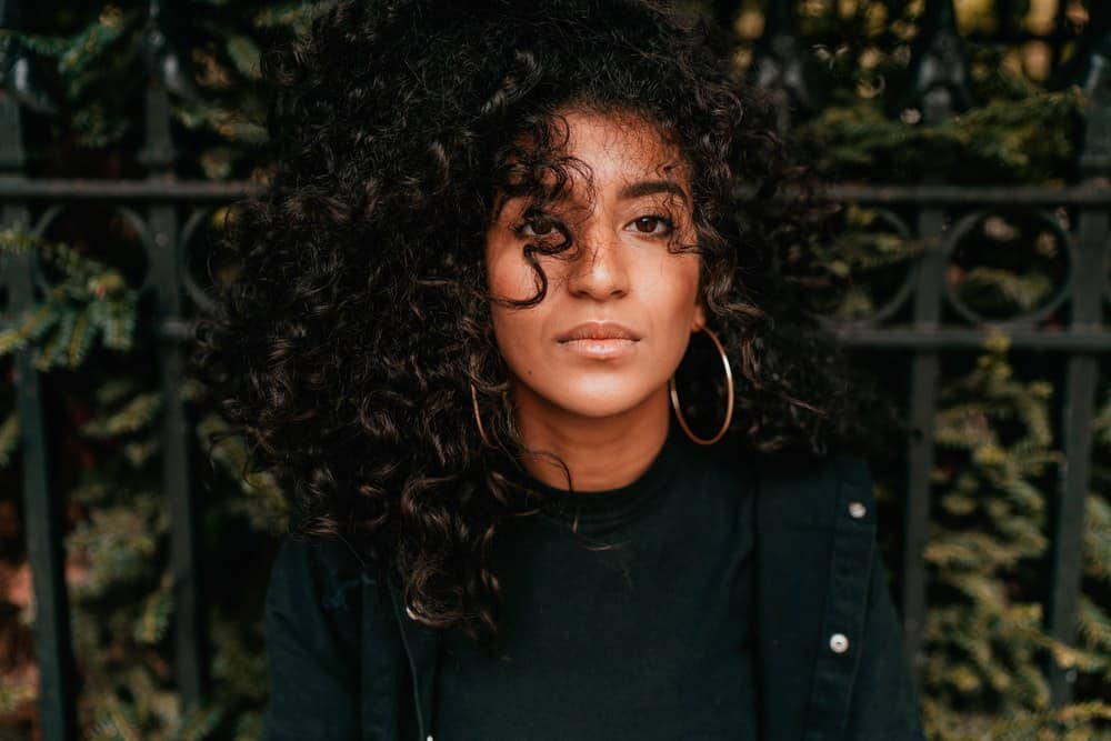 Women sitting on a park bench with sunflower oil treated hair wearing bronze earrings, curly hair and a green jacket.