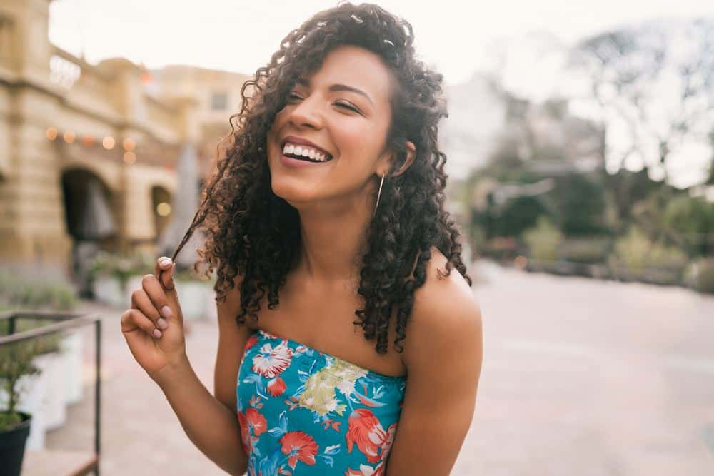 Beautiful Latin confident woman pulling a hair strand that cover in almond oil laughing in the city street.