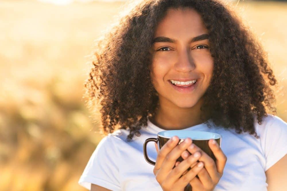 Beautiful mixed race female smiling with perfect teeth wearing a white t-shirt while drinking coffee outdoors.