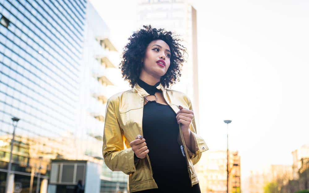 Beautiful African American young woman wearing a gold jacket and black dress with curly hair.