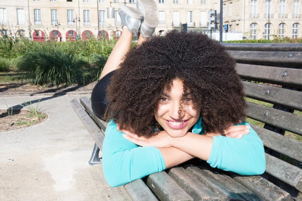 Young beautiful mixed race American woman lying on a bench in the city with naturally curly hair.