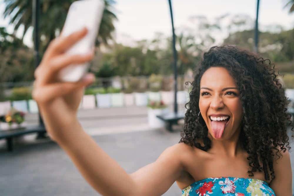 Young African American Latin woman taking a selfie with mobile phone outdoors in the street.