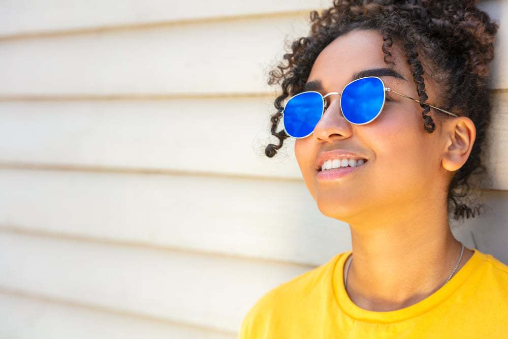 Cute girl with coconut oil treated hair wearing blue sunglasses and a yellow t-shirt on vacation smiling in summer sunshine.