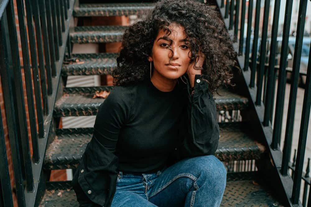 Black women with natural hair treated with sunflower oil sitting on the stairs of an apartment complex, wearing a black mock turtle neck shirt and blue jeans.