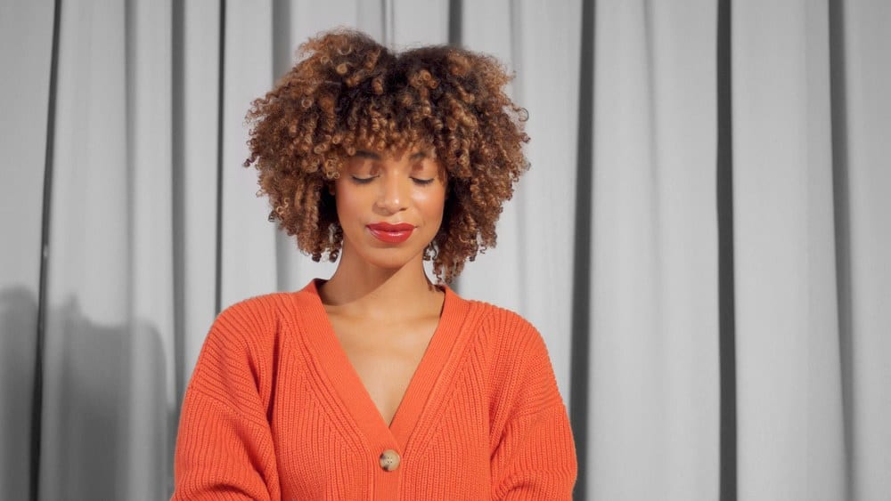 Cute African American female with a tight textured 3b curly afro hair in bright orange jacket with natural makeup for dark skin tones looking down at the ground.