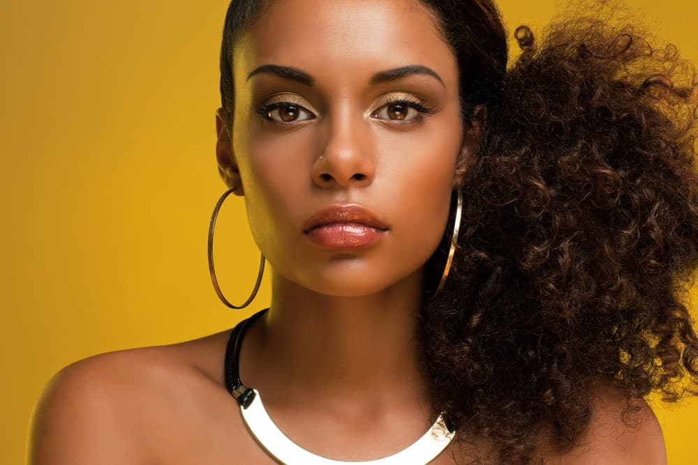 Pretty black women with a curly ponytail hairstyle looking directly into the camera wearing gold ear rings, a nose ring, gold necklace and redish pink lipstick.
