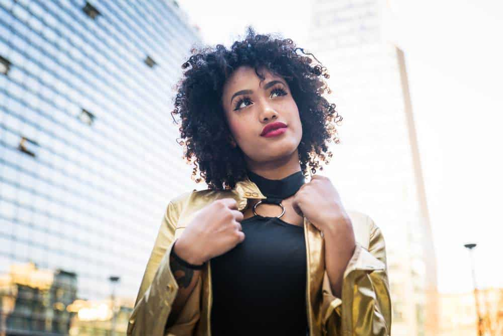 Black girl wearing a gold jacket and black dress with curly type 3b hair and red lipstick.
