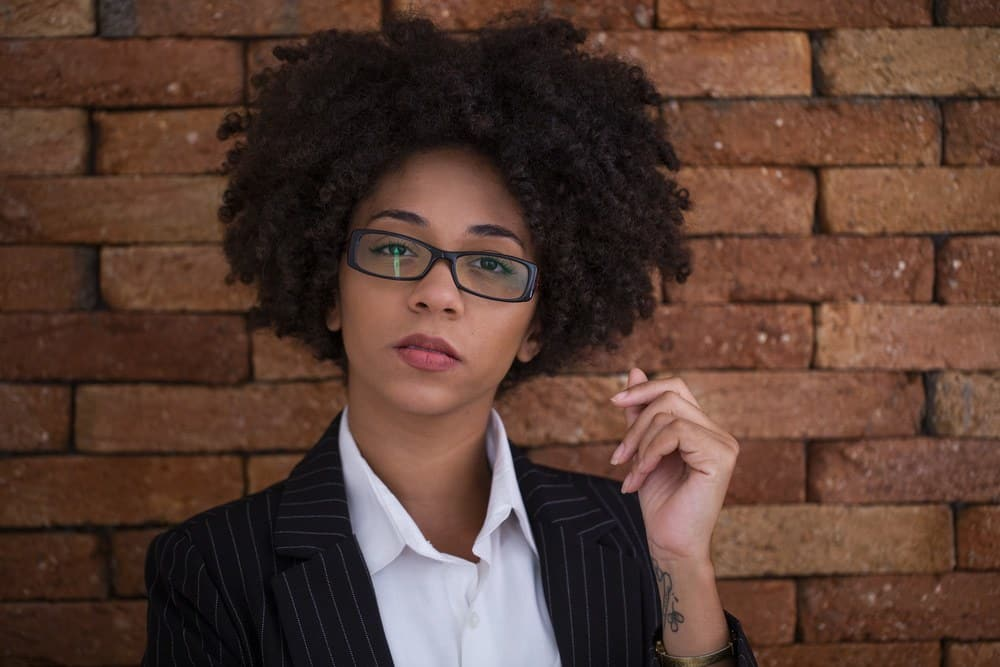 Beautiful African American business woman wearing glasses in the office standing in front of a brick wall.