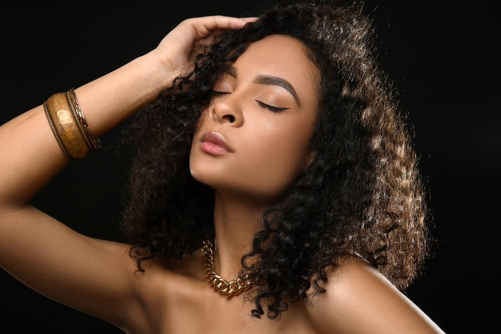 Portrait of beautiful African-American woman on dark background with a wavy hairstyle and a gold necklace.