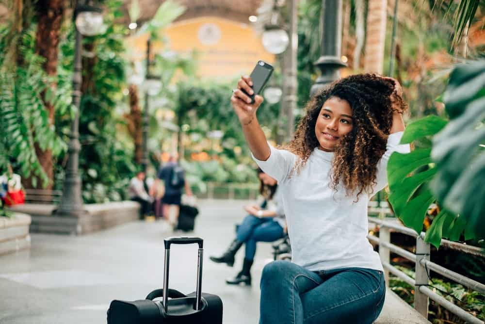 Lovely tourist African American girl taking selfie with thyme oil treated curly hair sitting in the mall.