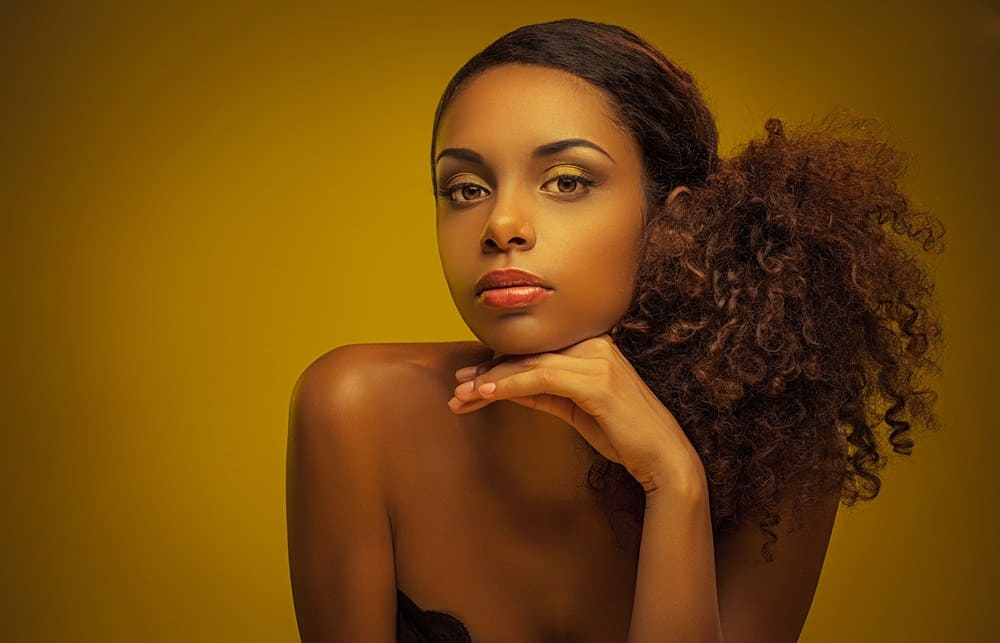 Portrait of a beautiful young African woman wearing a naturally curly ponytail.