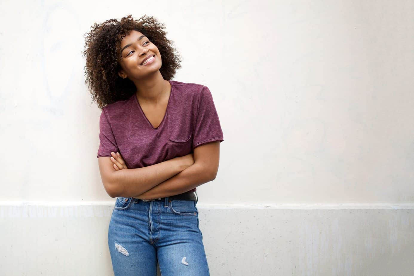 Cute black female with her arms crossed wearing a purple t-shirt and jeans