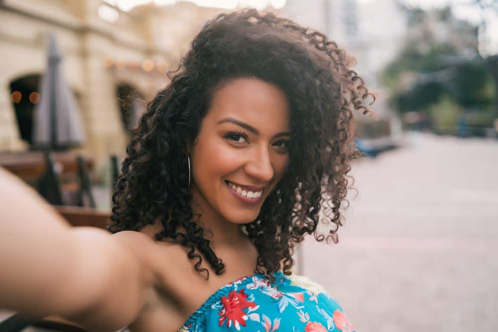 Young African American woman taking a selfie outdoors in the street.