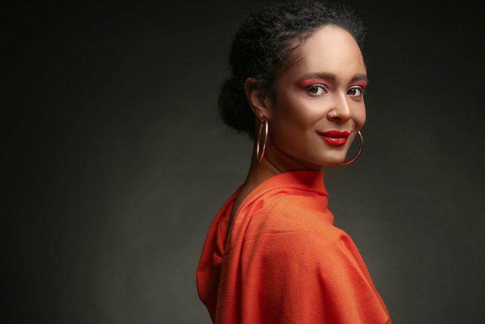 Portrait of beautiful African-American woman on dark background.
