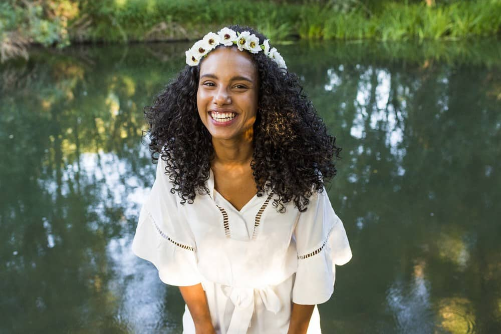 Outdoor photo of a cute young black woman standing in front of the water with type 3b curly hair.