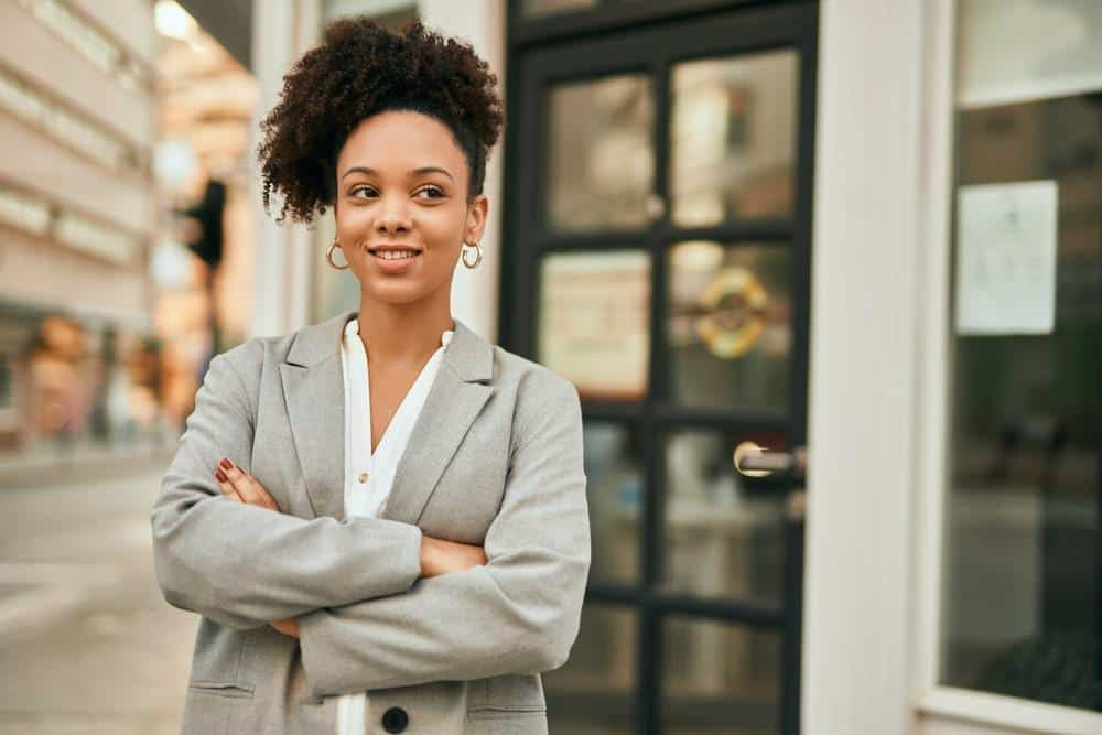 Young African American businesswoman with arms crossed standing at the city, smiling with gold ear rings, and a curly pineapple hairdo that's been treated with peppermint oil.