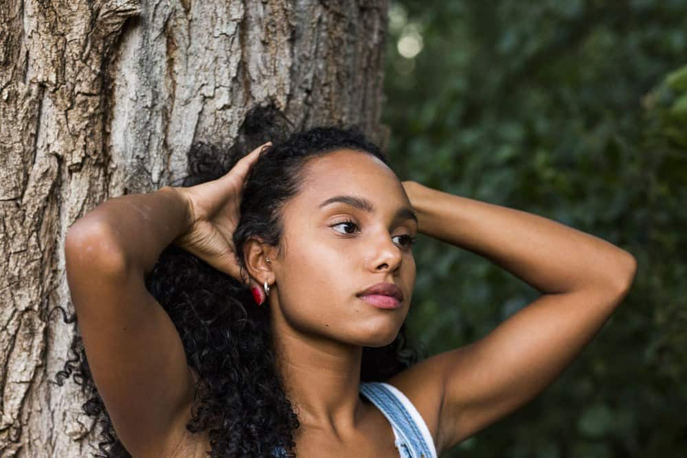Light skinned biracial women with curly hair standing in front of a tree with her hands creating a ponytail.