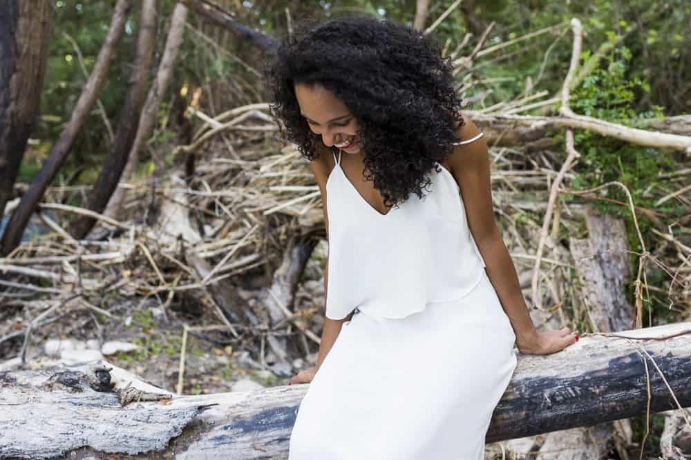 Beautiful young African American woman with clary sage oil treated hair at sitting on tree batch at sunset wearing a white dress.