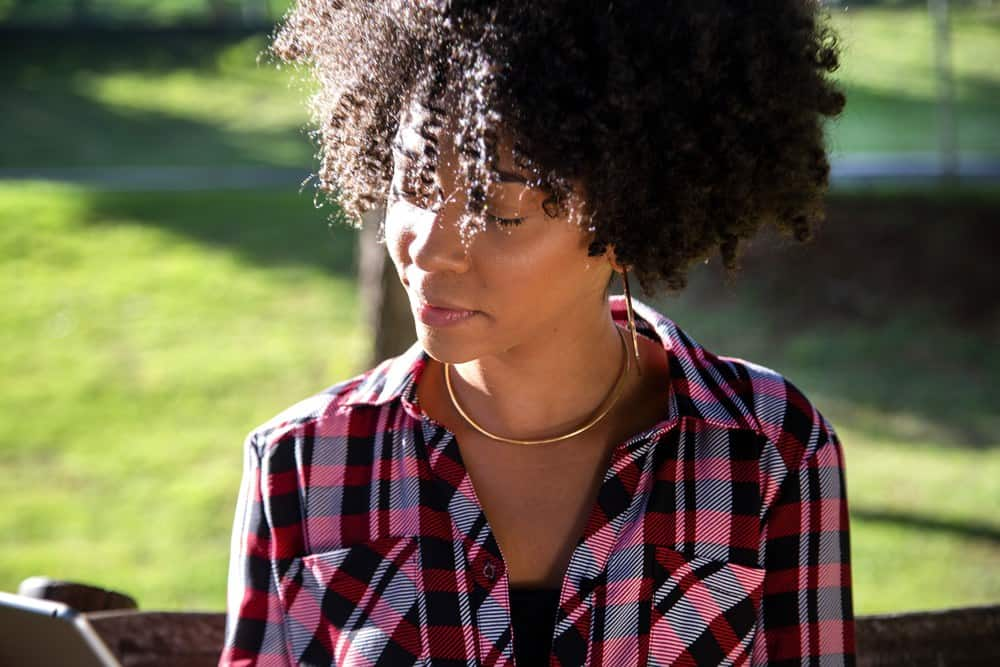 Young beautiful Brazilian female with black curly Afro hair with tablet, while sitting outdoors on the wooden bench in a park