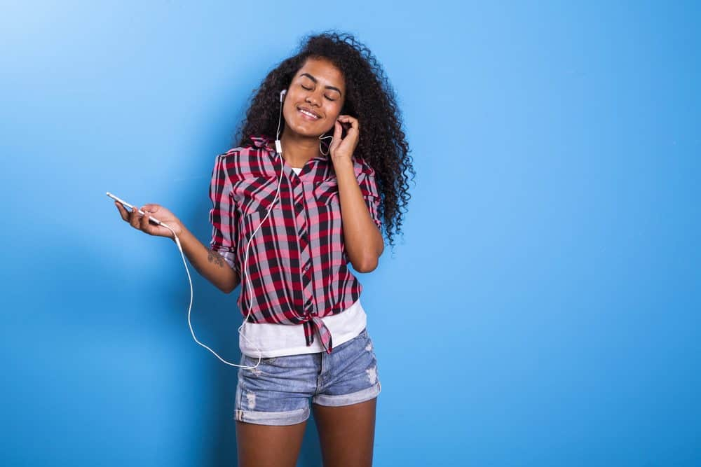 Cute amazing Indian American woman, dancing while listening to ipod music in apple head phones wearing a plaid shirt and blue jean shorts.