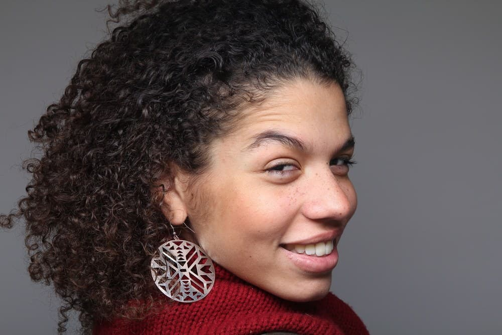 Latino female wearing a red sweater, silver earrings, and ombre type 3c curly hair look back at the photographer while taking a picture.
