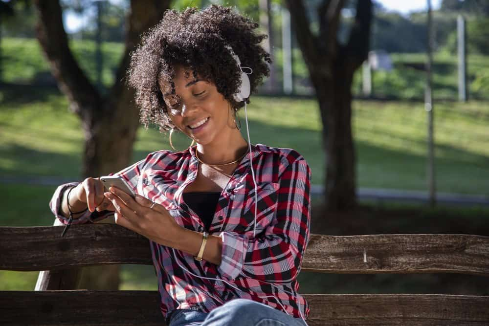 Young African American woman listening to music on cell phone.