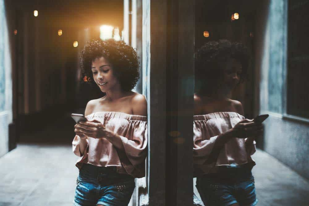A cheerful young Brazilian female with a medium curly hairstyle is leaning against the wall on a partly dark street corner.