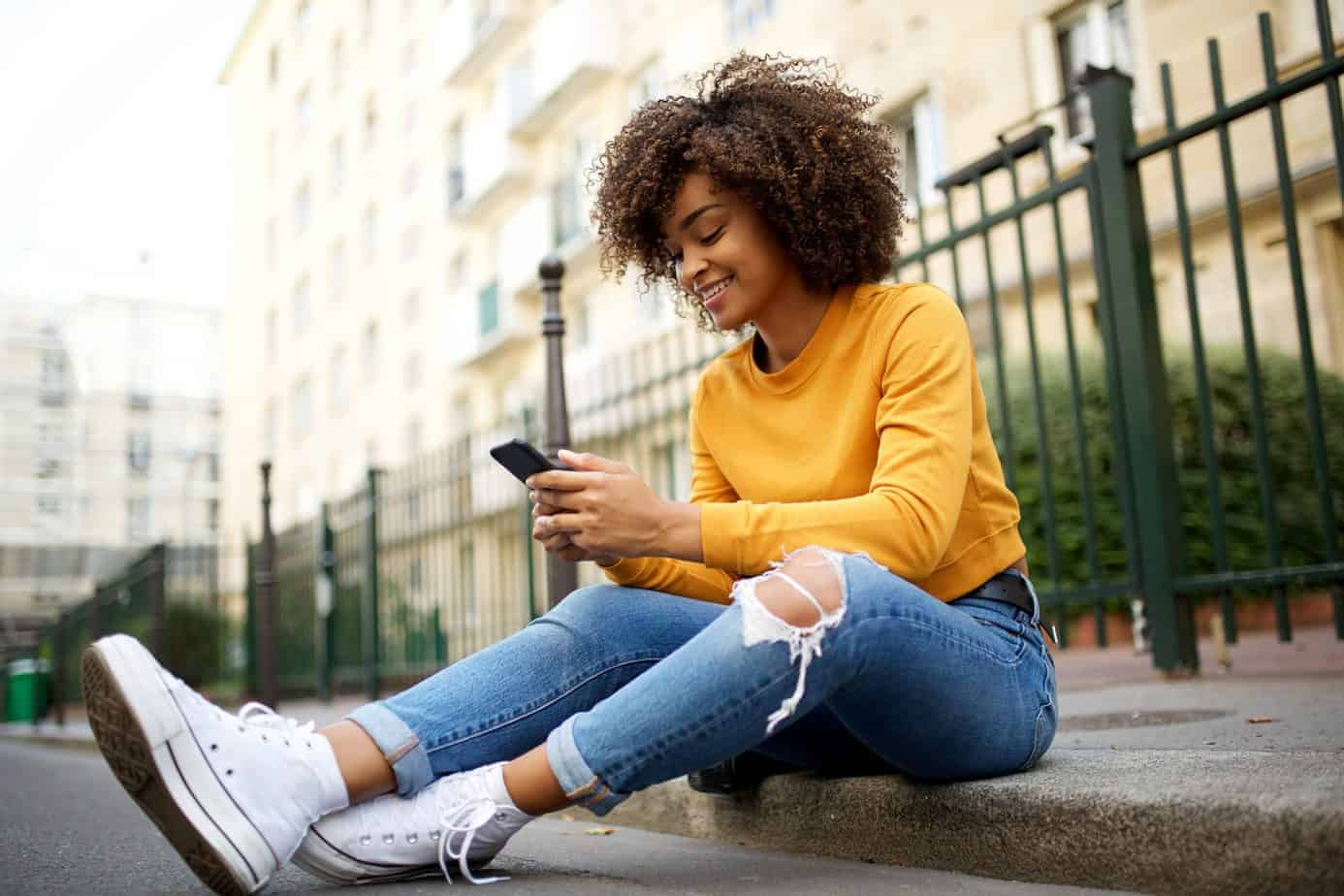 Beautiful African American female with curly hair sitting on a curb using her mobile phone wearing jeans, a yellow shirt and converse.