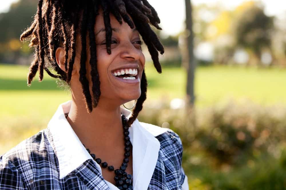 Young woman laughing after installing loc extensions in her 4c naturally curly hair.