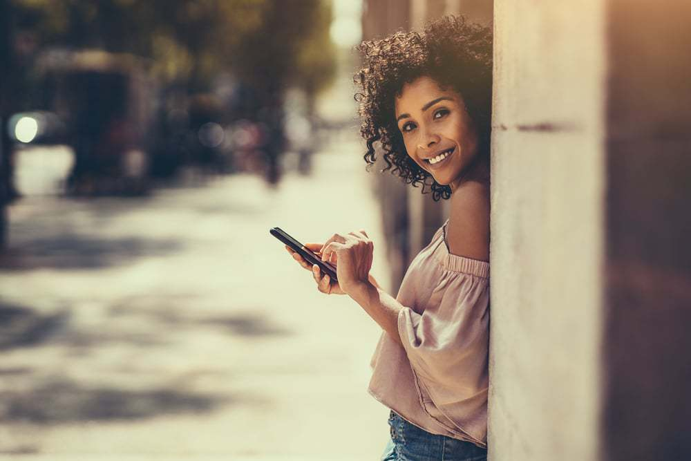 A young cheerful flirtatious curly-hair biracial female outdoors is leaning against the stone column while typing a message using the smartphone.