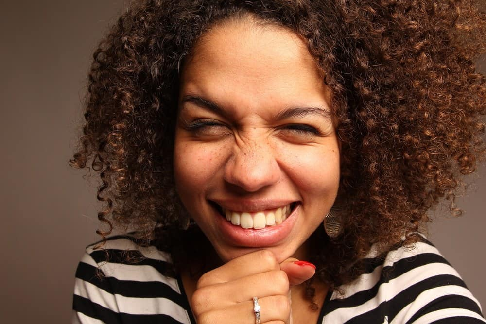 Beautiful black female with naturally curly hair wearing a diamond ring, gold earrings, red fingernail polish and pink lipstick.