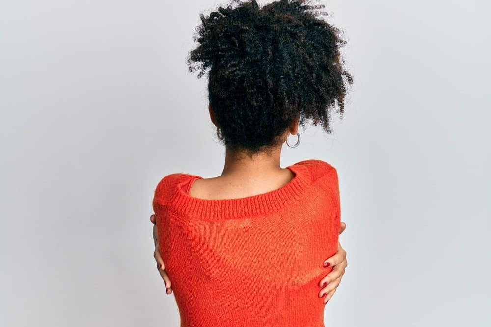 Young African American girl wearing casual clothes hugging herself from the back. She's showing self love and self care.