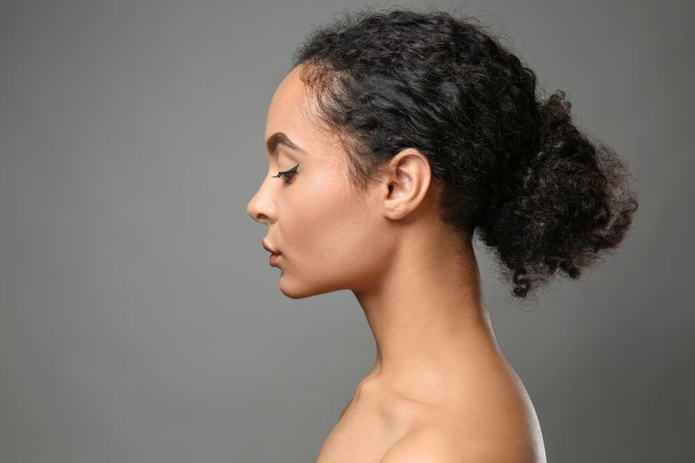 Portrait of beautiful African-American woman on grey background showcasing her natural hair. Hair appears to be type 3a according the Andre Walker System.