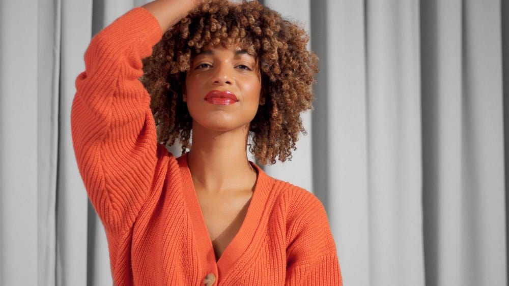 Closeup portrait of mixed race black woman with textured curly afro hair in bright orange jacket with natural makeup for dark skin tones.