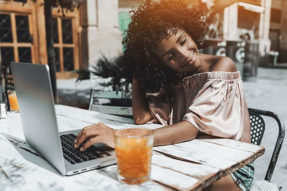 A dazzling young curly hair Brazilian female with straw curls admiring her hairstyle enjoying the sun while sitting in a cafe outdoors with her laptop and the glass of orange drink.