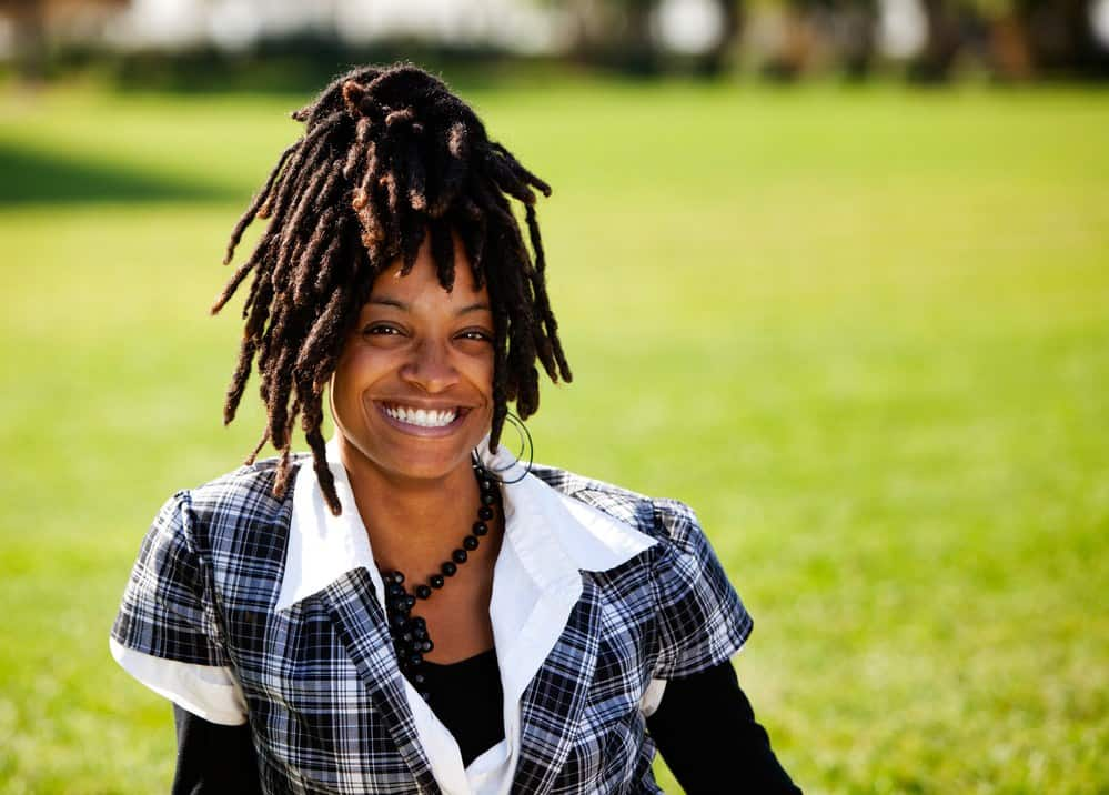 A beautiful African American with candid smile sitting in the yard of a huge lawn.